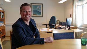 Muonion uusi kunnanjohtaja Lasse Peltonen hymyilee työhuoneessaan.