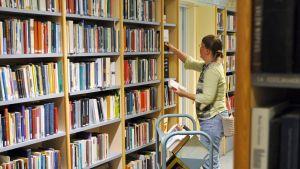 kirjastonhoitaja täyttää hyllyjä