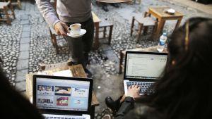 Ihmisiä kannettavien tietokoneiden kanssa kahvilassa Istanbulissa.