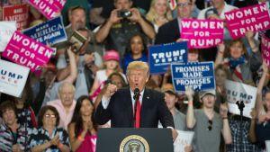 Kuvassa Trump puhujalavalla taustallaan hurraavia kannattajia kylttiensä kanssa.