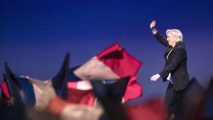 Marine Le Pen vilkuttaa kannattajilleen joukkokokouksessa. Hänellä on tumma housuasu. Etualalla näkyy Ranskan lippuja.