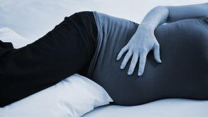 raskaana oleva nainen makaa sängyllä