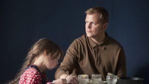 Stilli elokuivasta, mies ja lapsi pöydän ääressä