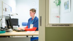 Osastonsihteeri Minna Romppainen istuu työpisteellään Kainuun keskussairaalassa.
