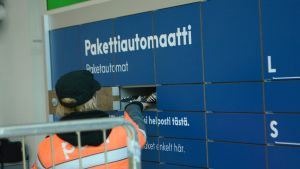 Kuljetusliikkeen työntekijä täyttää postin pakettiautomaattia Kuopion Prismalla.