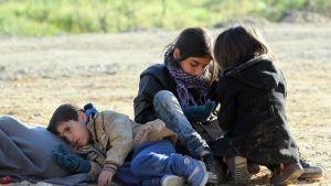 Poika makaa hiekalla, kaksi tyttöä istuu vieressä