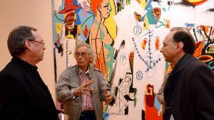 Miehiä taiteilija Basquaitin teoksen edessä.