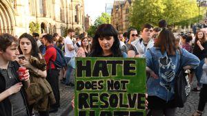 """Suuri joukko ihmisiä seisoo kaupungintalon edessä. Taustalla näkyy viktoriaanista uusgotiikkaa edustava kaupungintalo. Etualalla on tummahiuksinen nuori nainen, jolla on käsissään kyltti. Siinä lukee mustilla isoilla kirjaimilla vihreällä pohjalla: """"Hate does not resolve hate."""""""