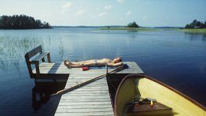 Mies makaa uimahousuissaan laiturilla.