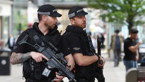 Kaksi raskaasti aseistettua poliisia seisoo kadulla. Miehillä on poliisin lippalakit ja parrat ja rynnäkköaseet.