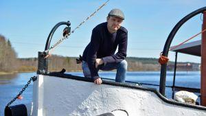Mies seisoo höyrlaivan keulassa telakalla.