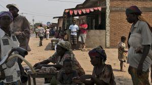 Naisia ja lapsia Burundin pääkaupungissa, Bujumburassa. Taustalla nuoret miehet seuraavat.