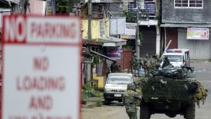 Filippiiniläissotilas juoksee panssariajoneuvon perässä kadulla. Edempänä kadun kulmassa seisoo lisää sotilaita. Kuvan vasemmassa reunassa etualalla näkyy pysäköintikieltokyltti.