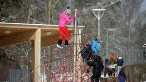 Koululaiset kiipeilevät kiipeilytelineessä välitunnilla koulun pihalla Kulosaaren ala-asteella Helsingissä maaliskuussa.