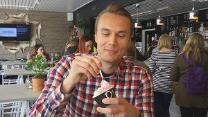 Yrittäjä Juha eskelinen maistelee oman tuotantolaitoksen gelato-jäätelöitä. Kupissa on mustikka- ja vaniljagelatoa.