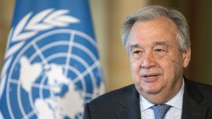 Antonio Guterres, taustalla YK:n lippu
