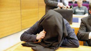 Syytetty peittää oikeussalissa kasvonsa.