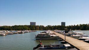 Moottoriveneitä laiturissa Tapiolassa. Taustalla näkyy Keilaniemessä sijaitsevat Nesteen ja Koneen tornitalot.