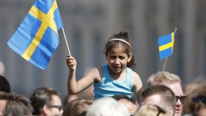 Pikkutyttö istuu aikuisen harteilla ja heiluttaa Ruotsin lippua.