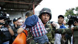 Sotilas kantaa lasta turvaan.