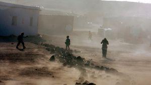 Pieni kylä, jotka hiekkamyrsky riepottaa. Ihmiset peittävät kasvonsa