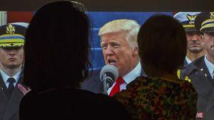 äiti ja lapsi, taustalla Trump televisiossa.