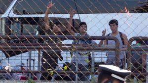 Turvapaikanhakijoita poistumassa Ateenan lentokentältä perjantaina.