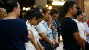 Filippiiniläisiä kokoontui perjantaina hartaustilaisuuteen asemiehen hyökkäyksen kohteeksi joutuneen kasinon eteen.