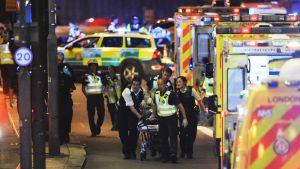 Poliisit saattavat iskussa loukkaantunutta uhria ambulanssiin.