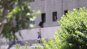 Poliisit avustavat ihmisiä ulos parlamenttirakennuksesta Teheranissa.