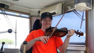 Tiina Jokela soittaa viulua lautalla.