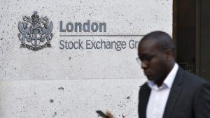 Mustaihoinen mies kävelee kadulla katsellen kännykkäänsä. Taustalla näkyy Lontoon pörssin kyltti.