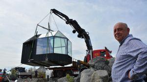 Rakennuksen kuljettaminen ja asentaminen kivikkoiseen ulkosaaristoon ei ole ihan pikkujuttu. Kalle`s Innin toimitusjohtaja Freddi Skott seuraa vierestä.