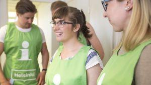Ihmisiä vihreät Helsinki-oppaan liivit yllään.
