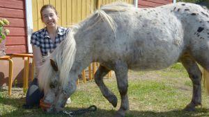 Liisa Koivisto hevosen kanssa tallin edustalla