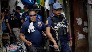 Joukko poliiseja kulkee ahtaalla kujalla. Kahdella etualalla olevalla poliisilla on mustat lasit ja tummansiniset pikee-paidat. Lippalakipäinen polisi pitelee oikeassa kädessään konepistoolia piippu maahan suunnattuna.