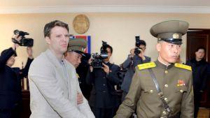 Kuvassa surullinen Otto Warmbier, jota vetää kädestä pohjoiskorealainen sotilas.