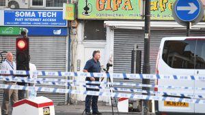 Kuvan keskiössä poliisimies seisoo jalustan päälle viritetyn kameran takana. Etualalla kulkevat poliisin eristysnauhat. Taustalla näkyy suljettuja liikkeitä.