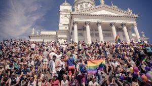 Ihmisiä istuu Tuomiokirkon portailla.