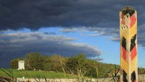 Musta-puna-keltaiseksi maalattu betonipylväs seisoo ruohikossa. Taivaalla musta pilviä.