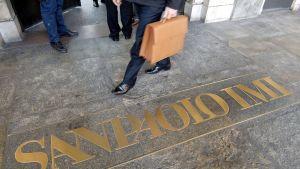 Mies astuu kadulle Sanpaolon pankista. Kadulla lukee kultaisin kirjaimin pankin nimi.