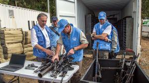 YK:n työntekijät vastaanottavat Farc-kapinallisten aseita Kolumbiassa.