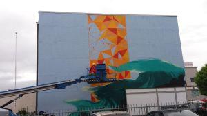 Tornioon maalataa muraalia.