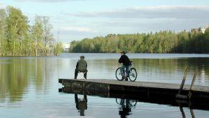 Mies kalastaa piippu suussa laiturilla, poika seuraa vierestä.