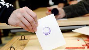 Äänestyslippu äänestäjän kädessä.