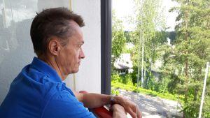 Hannu Haimi katsoo parvekkeelta pihalle
