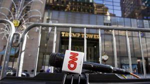 Etualalla kuvassa näkyy CNN:n logolla varustettu mikrofoni rauta-aidan edessä. Taustalla näkyy rakennus, jossa oven päällä lukee isoilla kullanvärisillä kirjaimilla Trump Tower.