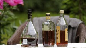 Vajaita alkoholipulloja kesäpöydällä.