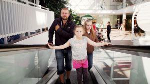 Ava ja Venla suojelevat isäänsä kauppakeskuksen rullaportaissa.