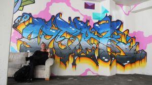 Taiteilija istuu sohvalla graffitin edessä
